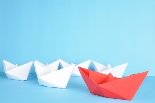 Red paper ship leads among white on blue. leadership concept.