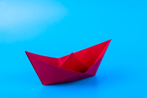 Red paper ship in new direction on blue background, new normal concept, copy space