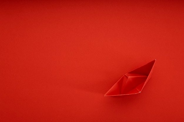 Red paper ship on red background