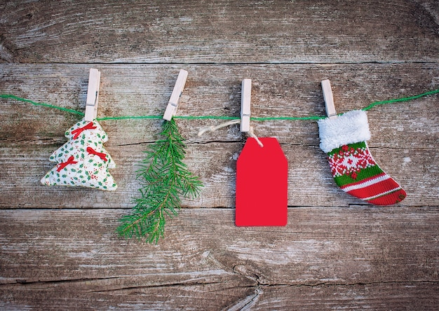 Red paper tag and christmas decorations hang on rope with clothespins