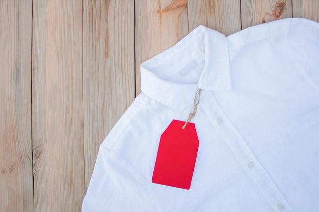 服の赤い紙のタグは白いシャツの上にあります