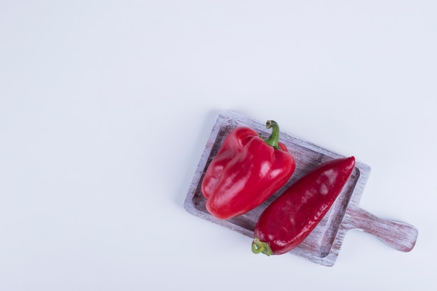 Red paprika and bell pepper on a wooden board.