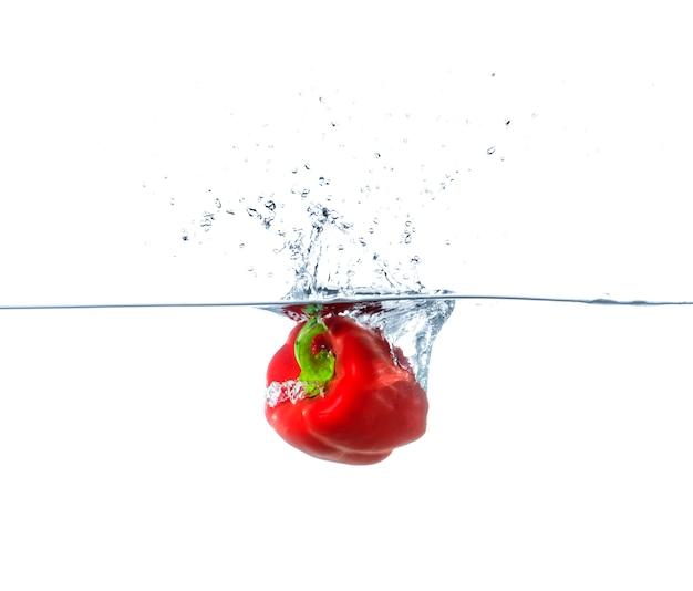 Red paprika falling in water