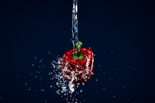 Red paprika pepper being washed under water.