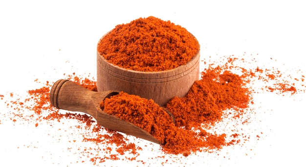 Red paprika powder in wooden bowl and scoop isolated on white