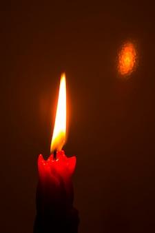 赤いパラフィンの哀愁を帯びた記念の厚いろうそくが黒い背景のクローズアップで燃える