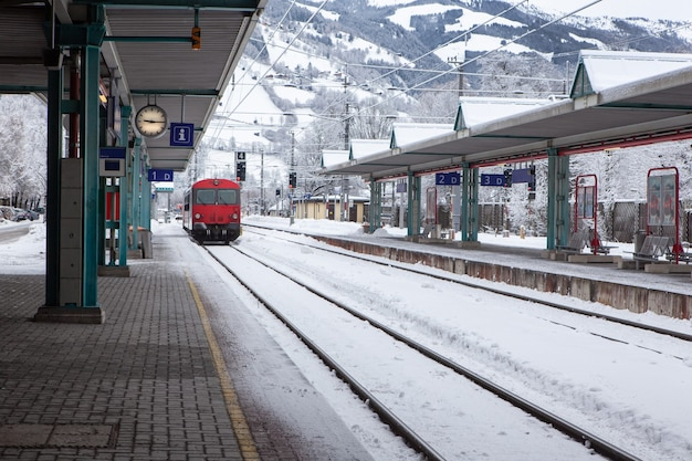 Red passenger high-speed train pulls up to stop at deserted snow-covered railway station in mountains.