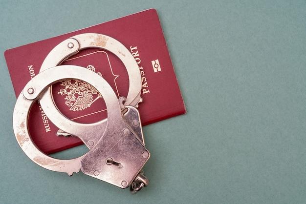Красный паспорт и наручники на зеленом фоне. документ, удостоверяющий личность человека.