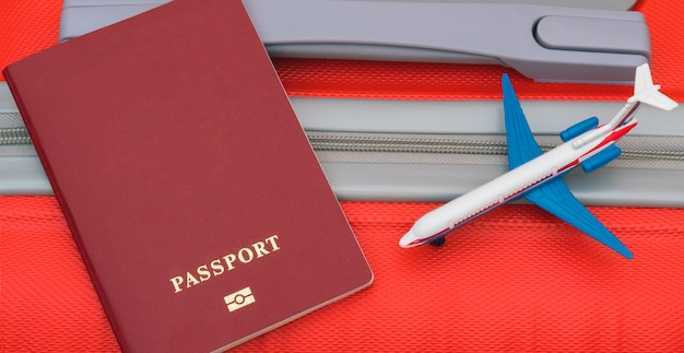 The red passport and model of the plane lie on the red suitcase.