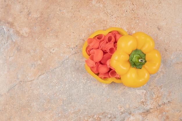 オレンジ色の背景にピーマンの赤いパスタ