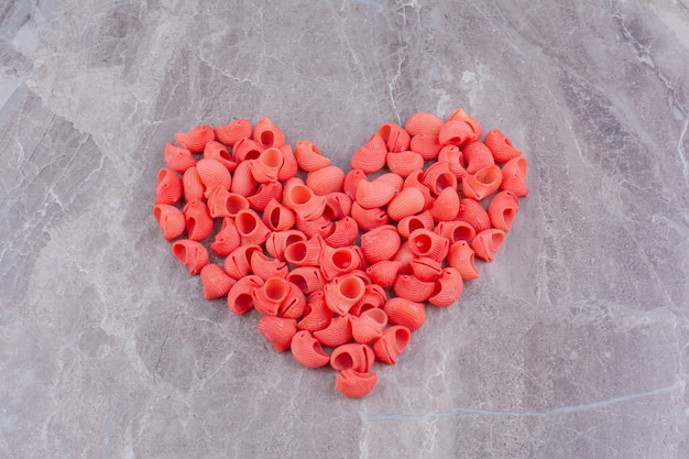 Red pastas in a heart shape on the marble surface