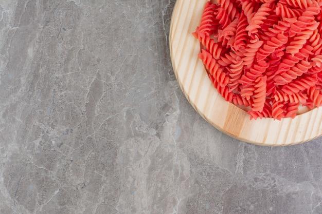 Красные макароны в томатном соусе на деревянной тарелке.