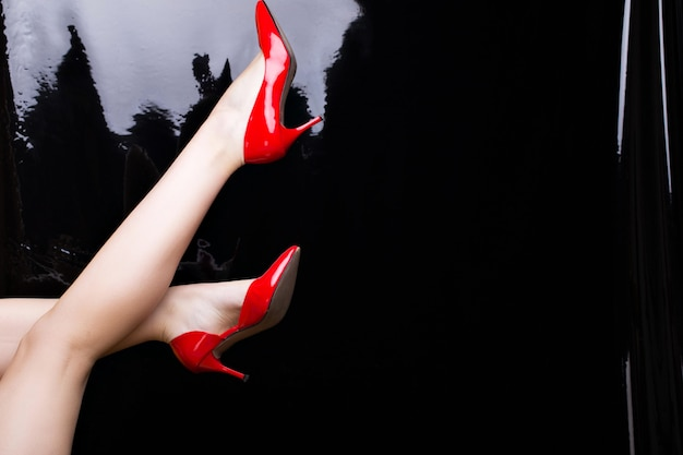 Red patent leather shoes on a black shiny background.