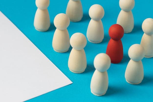 Pedone rosso circondato da quelli bianchi accanto alla carta bianca