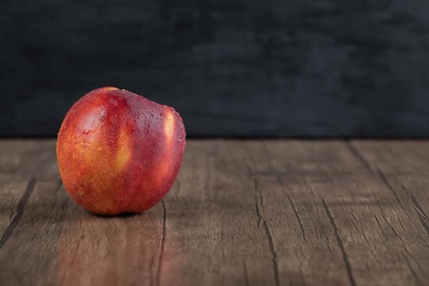 Pesche rosse isolate sulla tavola di legno.
