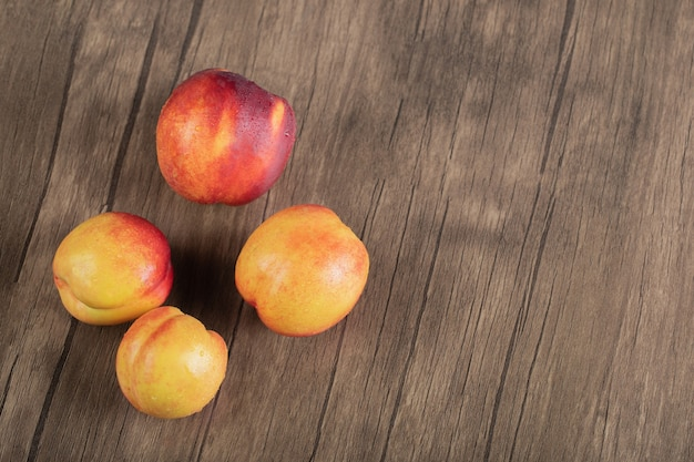 Red peaches isolated on the wooden table.