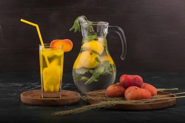 Красные персики со стаканом сока и лимонада в банке