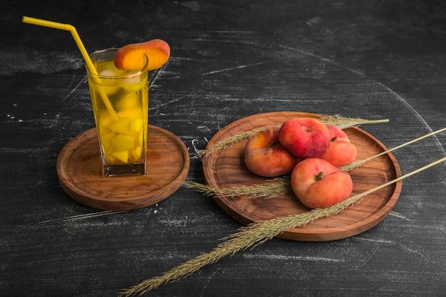 木製の大皿にジュースのグラスと赤桃