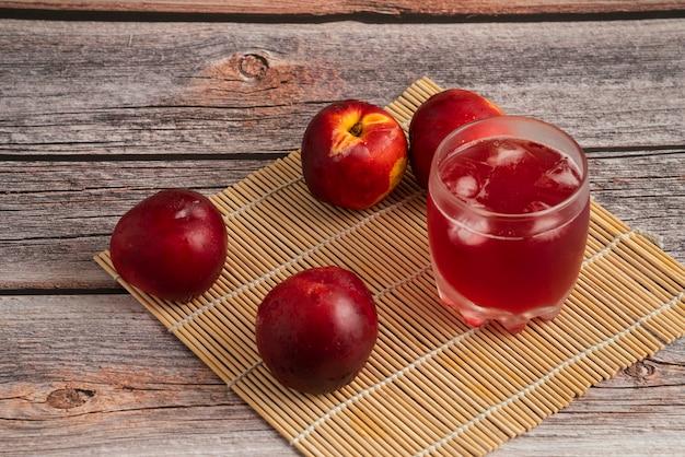 Pesche rosse con una tazza di bevanda ghiacciata