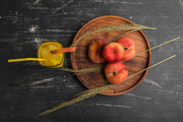 Red peaches with a glass of juice in a wooden platter, top view