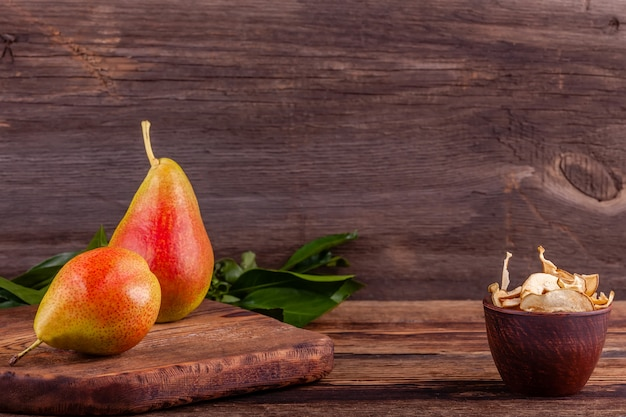 Red pears with sliced homemade dried fruits in wooden cup, healthy food concept