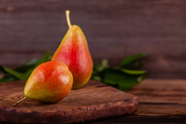 Red pears on wooden background, concept of healthy and vegan food, copy space