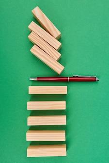 Красная ручка и простые деревянные блоки на зеленом