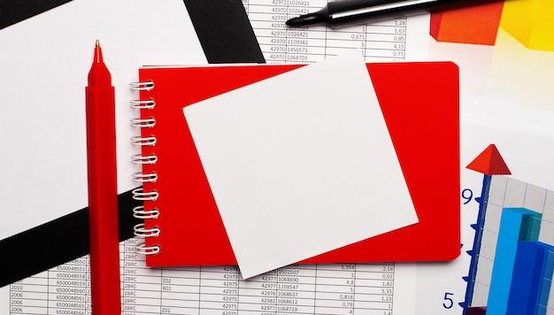 Красная ручка, черный маркер, цветные таблицы, красный блокнот и белый чистый лист бумаги