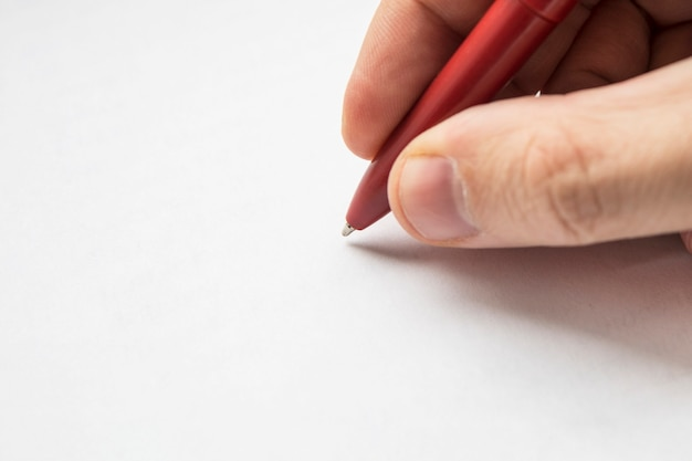 Red pen in hands close up. right hand with pencil and left empty over a white blank sheet of paper lying on table. empty space for design