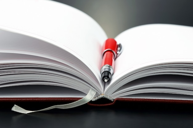 開いているノートに横たわっている赤いペン