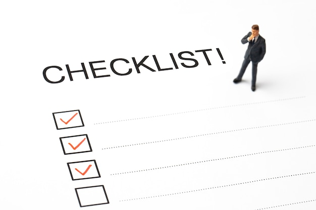 Red pen marking on checklist box with miniature business man