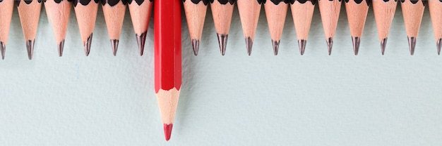 Red pencil is longer than black in background closeup