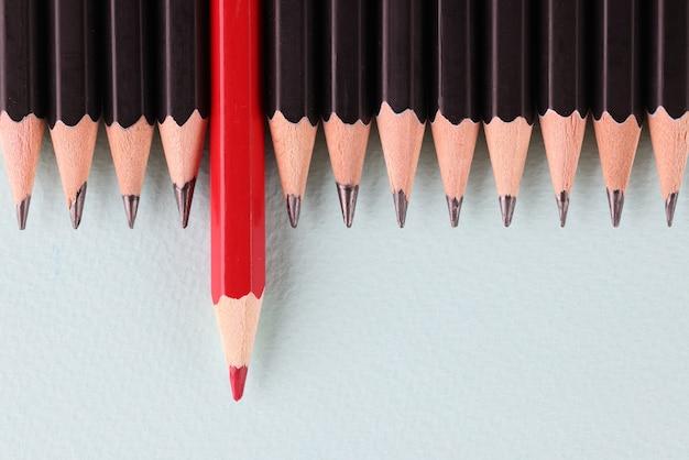 Красный карандаш длиннее черного на фоне крупным планом
