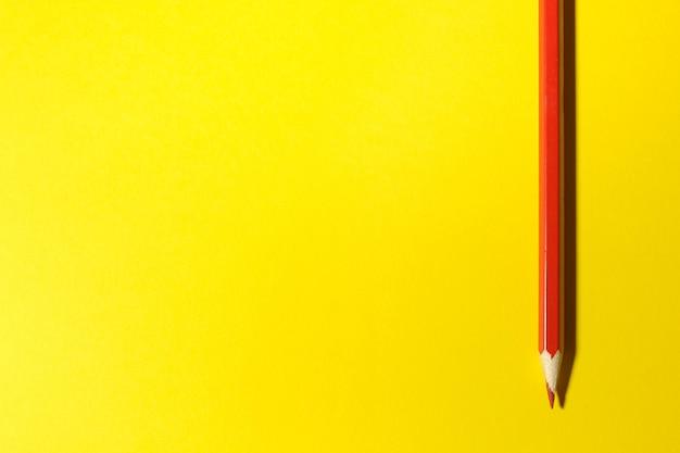 Красный карандаш на ярко-желтом фоне. место для текста. вид сверху