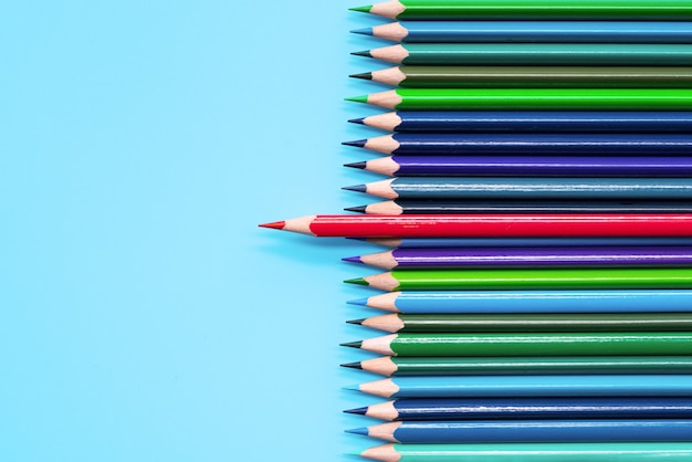 Red pencil standing out on blue background. leadership, uniqueness