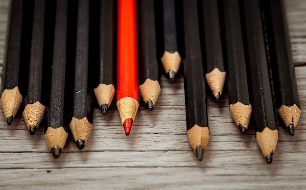 Red pencil stands out from the crowd of black pencil on a wooden white background.