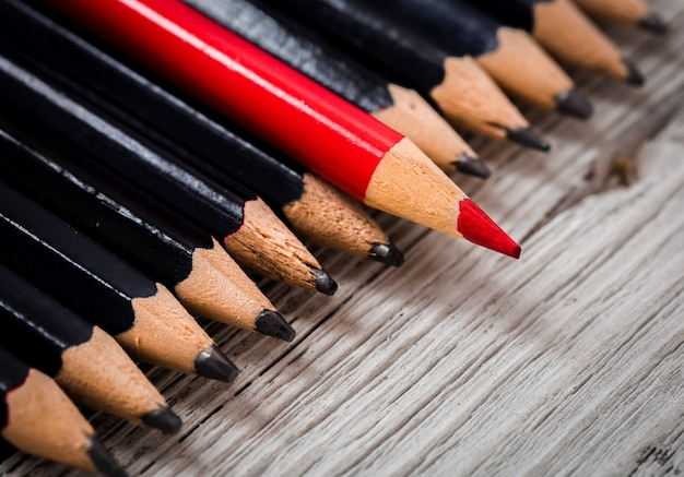 Red pencil stands out from the crowd of black  on a wooden white table