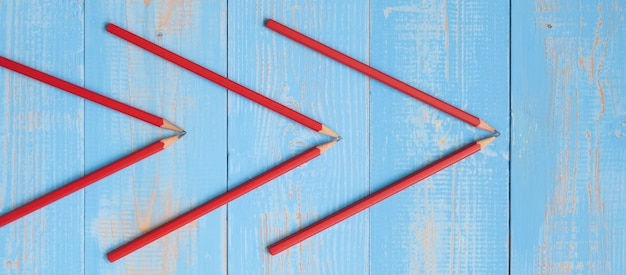 Red pencils of arrow shape on blue wooden background.