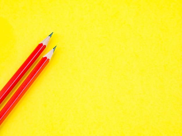 黄色の背景に赤い鉛筆。教育とビジネスコンセプト。