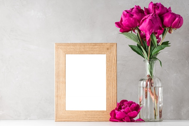 Red peony flowers bouquet with blank photo frame on white.