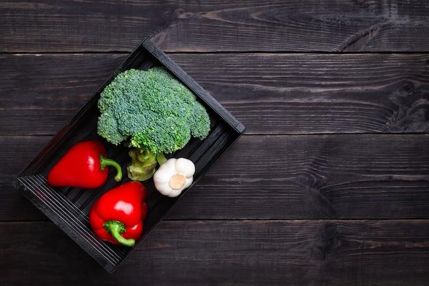 Красный перец, брокколи и чеснок в коробке на черном фоне. концепция овощей для поддержания иммунитета. копировать пространство