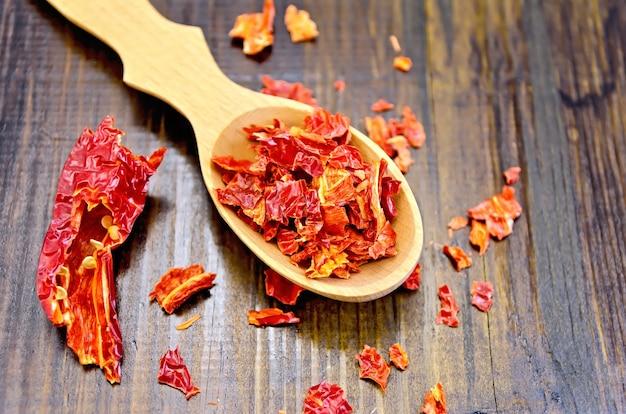 木のスプーンの赤唐辛子フレークと木の板の乾燥赤唐辛子のポッド