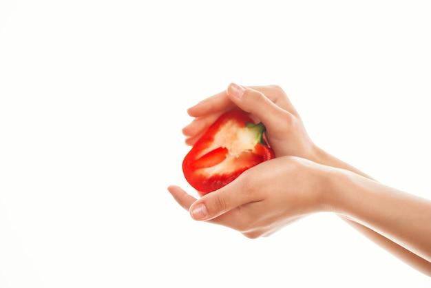 Красный перец в руке, порезанные пополам ингредиенты для салата. фото высокого качества
