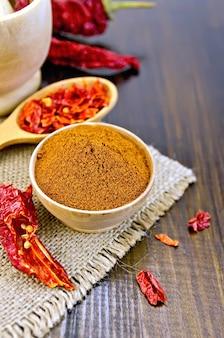 木製のボウルに赤唐辛子の粉、木のスプーンと乳鉢にシリアルと乾燥唐辛子のさや、木の板に袋に入れます