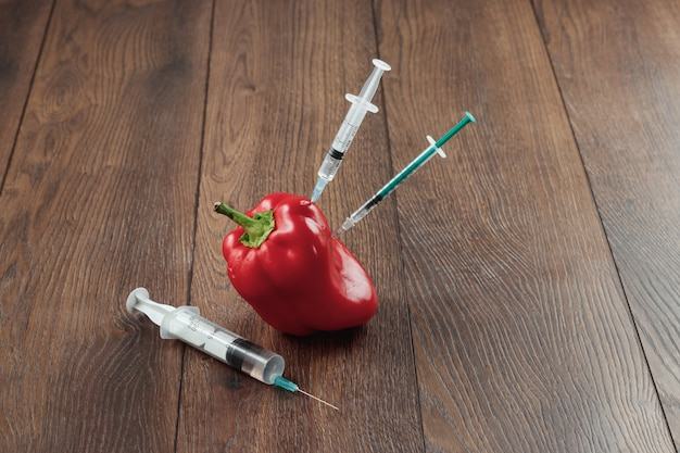 Red pepper and stuck in it a syringe on a wooden background