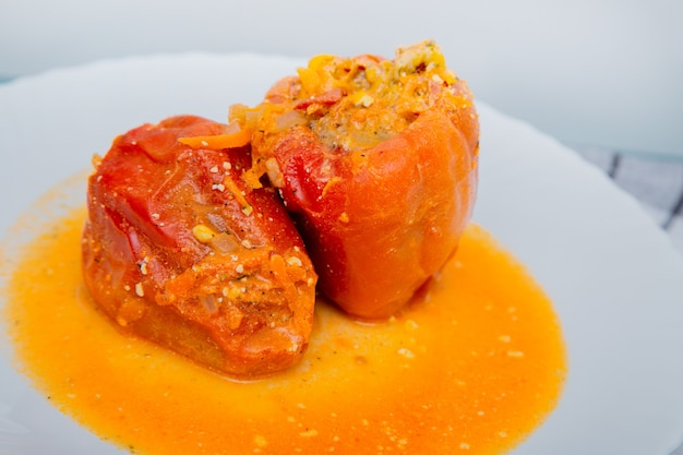 Red pepper stuffed with minced meat and carrots with onions lies on a white plate which stands on a ...