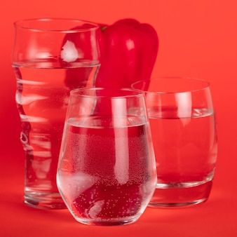Red pepper surrounded by glasses of water
