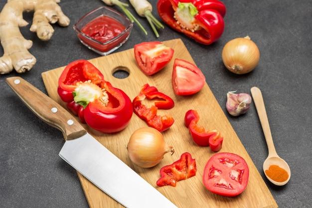 まな板に赤唐辛子、トマト、ナイフ。生姜の根、玉ねぎ、スプーンをテーブルに。黒の背景。上面図