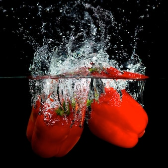 Red pepper in water with splashes