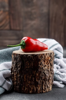 Red pepper on a wooden piece with picnic cloth side view on grey and stone tile wall